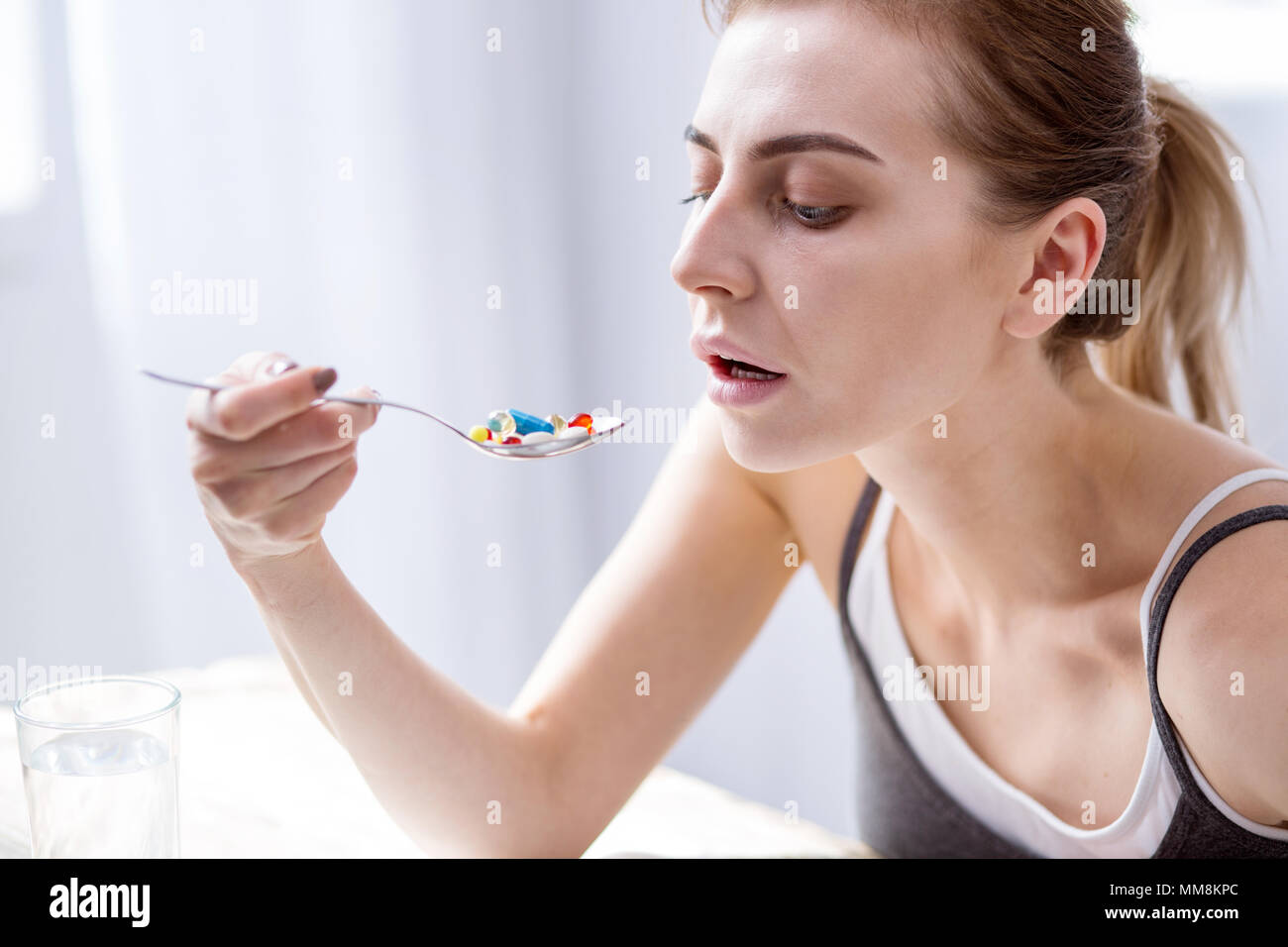 Sad young woman looking at the pills Photo Stock
