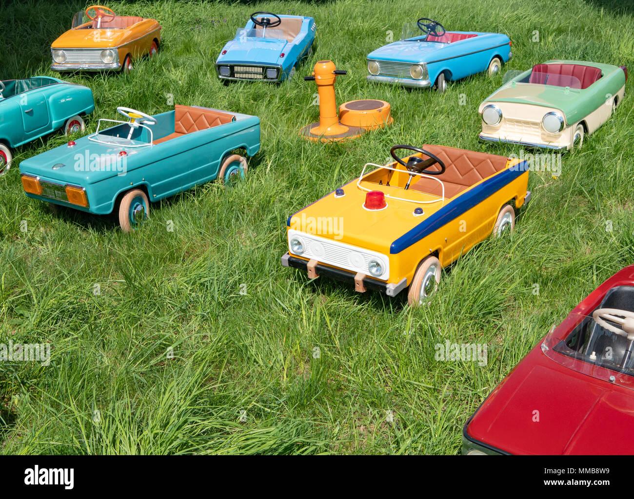 De nombreux jouets anciens de voitures à pédales pour enfants sur l herbe  verte à l aire de jeux 38fe9addce45