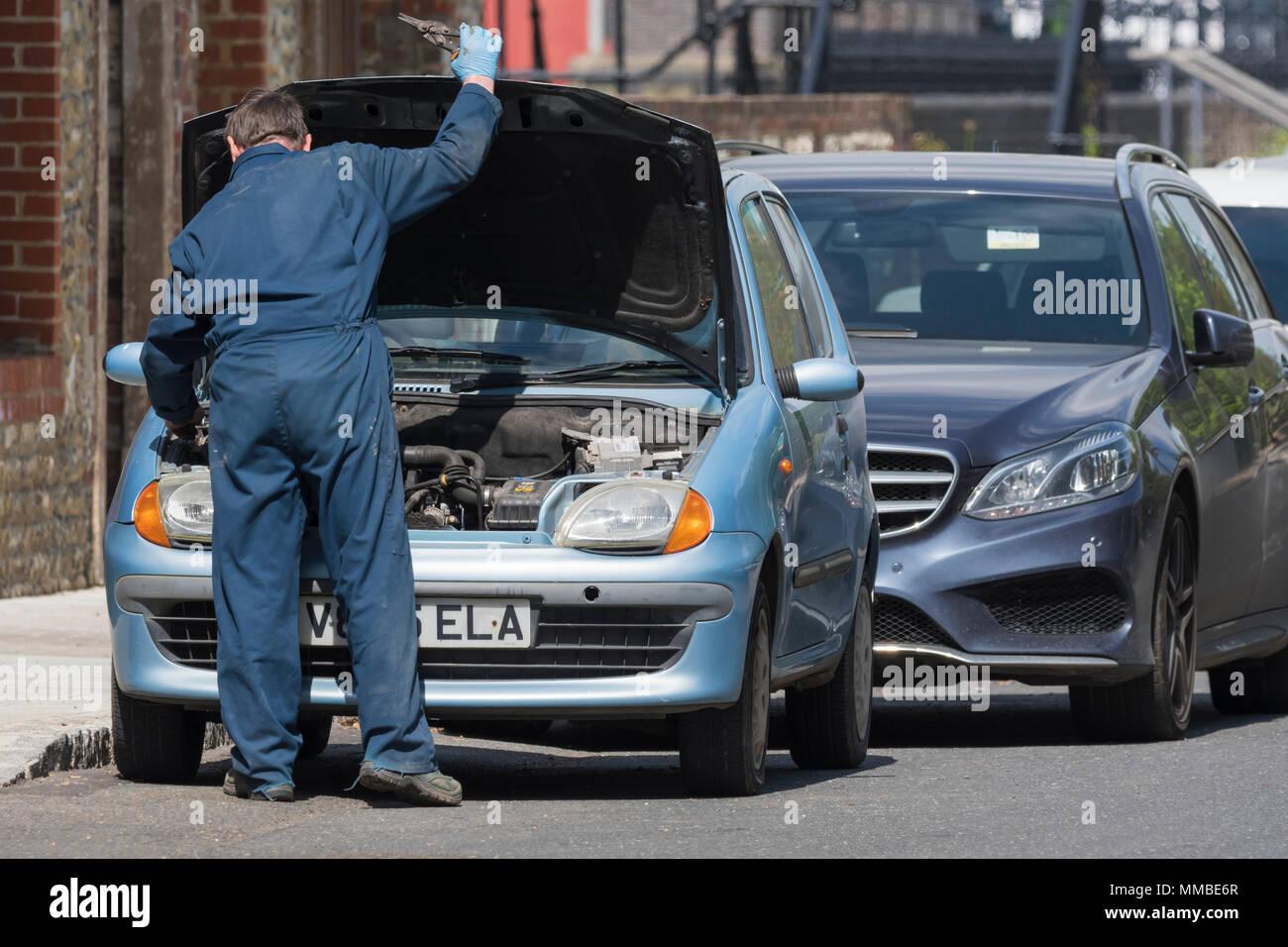 Mécanicien de voiture portant des salopettes de travail sur une voiture avec le capot jusqu'au Royaume-Uni. Photo Stock