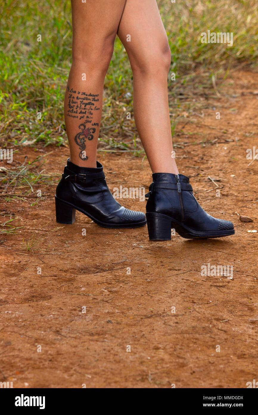 bottes noires et tatouage sur la jambe banque d'images, photo stock