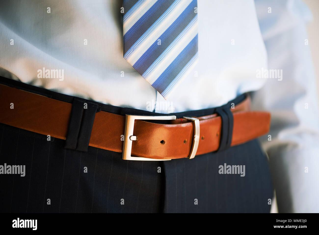 2e4ac805a5c Homme porte la ceinture. Jeune homme en costume décontracté avec des  accessoires. Vêtements de mode et concept. Le marié se préparer le matin  avant de ...