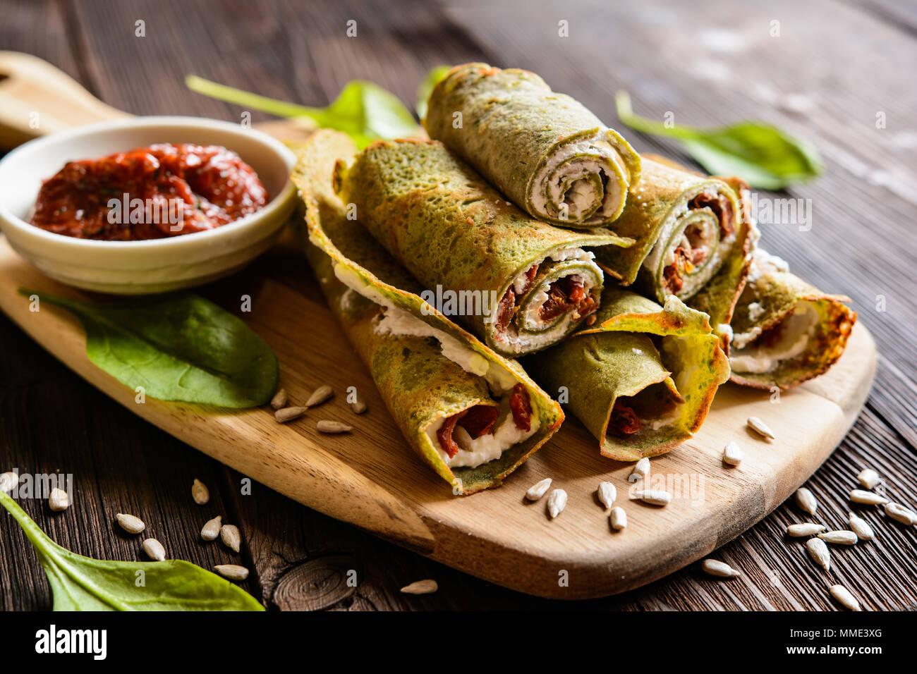 Salé crêpes farcies aux épinards, fromage feta, tomates séchées et graines de tournesol Photo Stock
