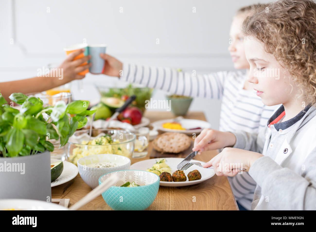 Boy eating falafel lors d'anniversaire à la maison. Régime alimentaire sain pour les enfants Photo Stock