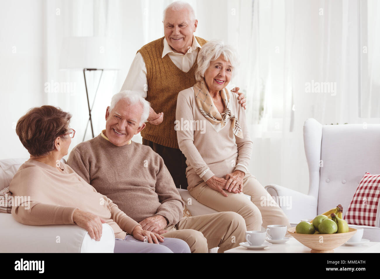 Deux couples relaxing together at home, talking and smiling Banque D'Images