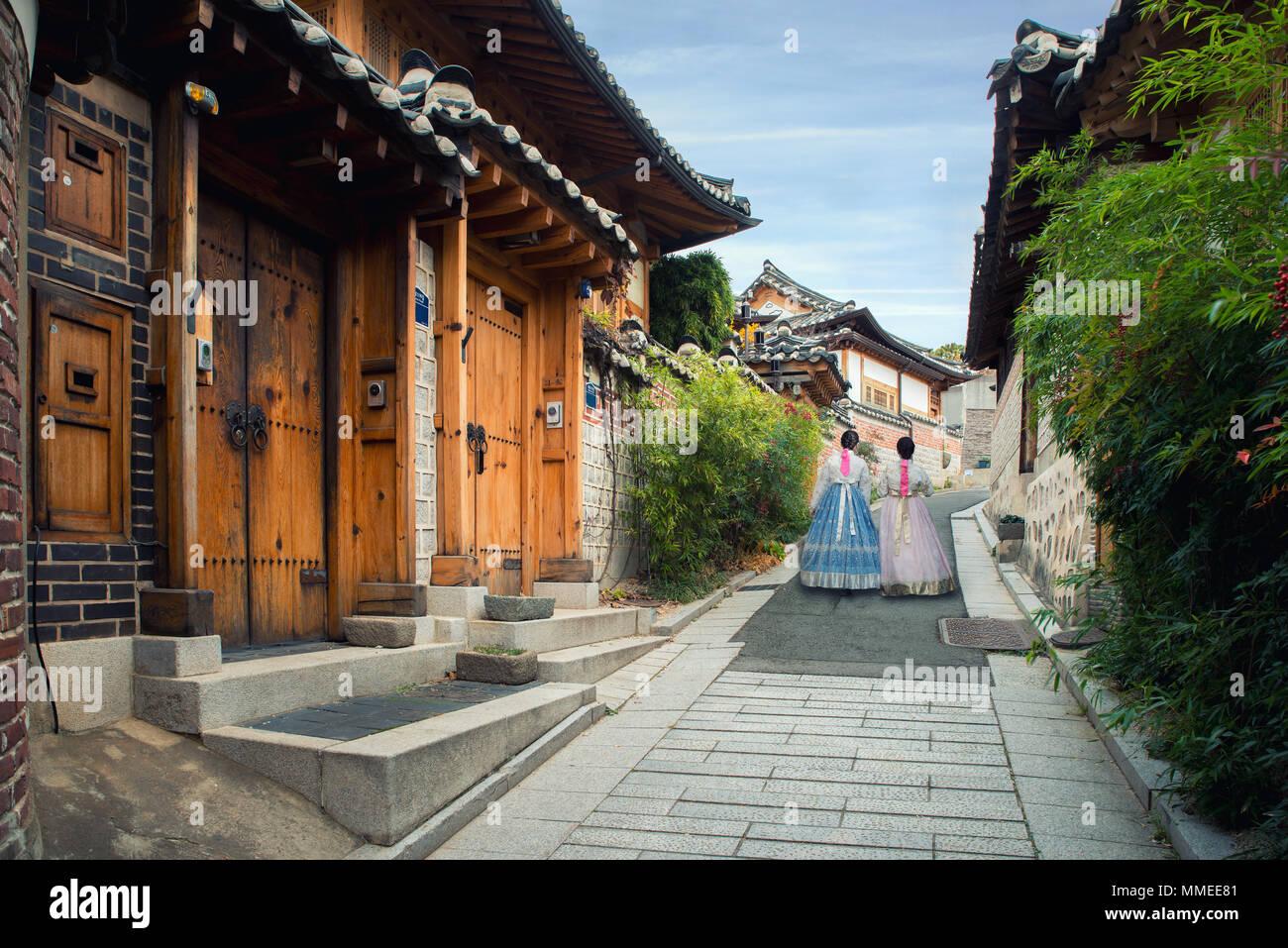Retour de deux femme portant hanbok marcher dans les maisons de style traditionnel du village de Bukchon Hanok à Séoul, Corée du Sud. Banque D'Images