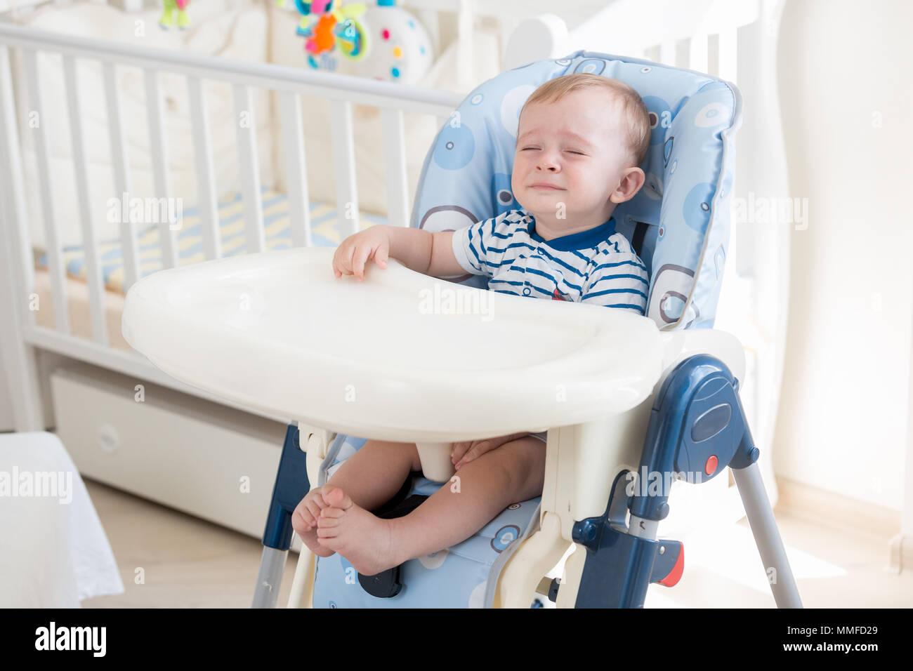 Lage De 10 Mois Bebe Garcon Assis Sur Une Chaise Haute Et Pleurer