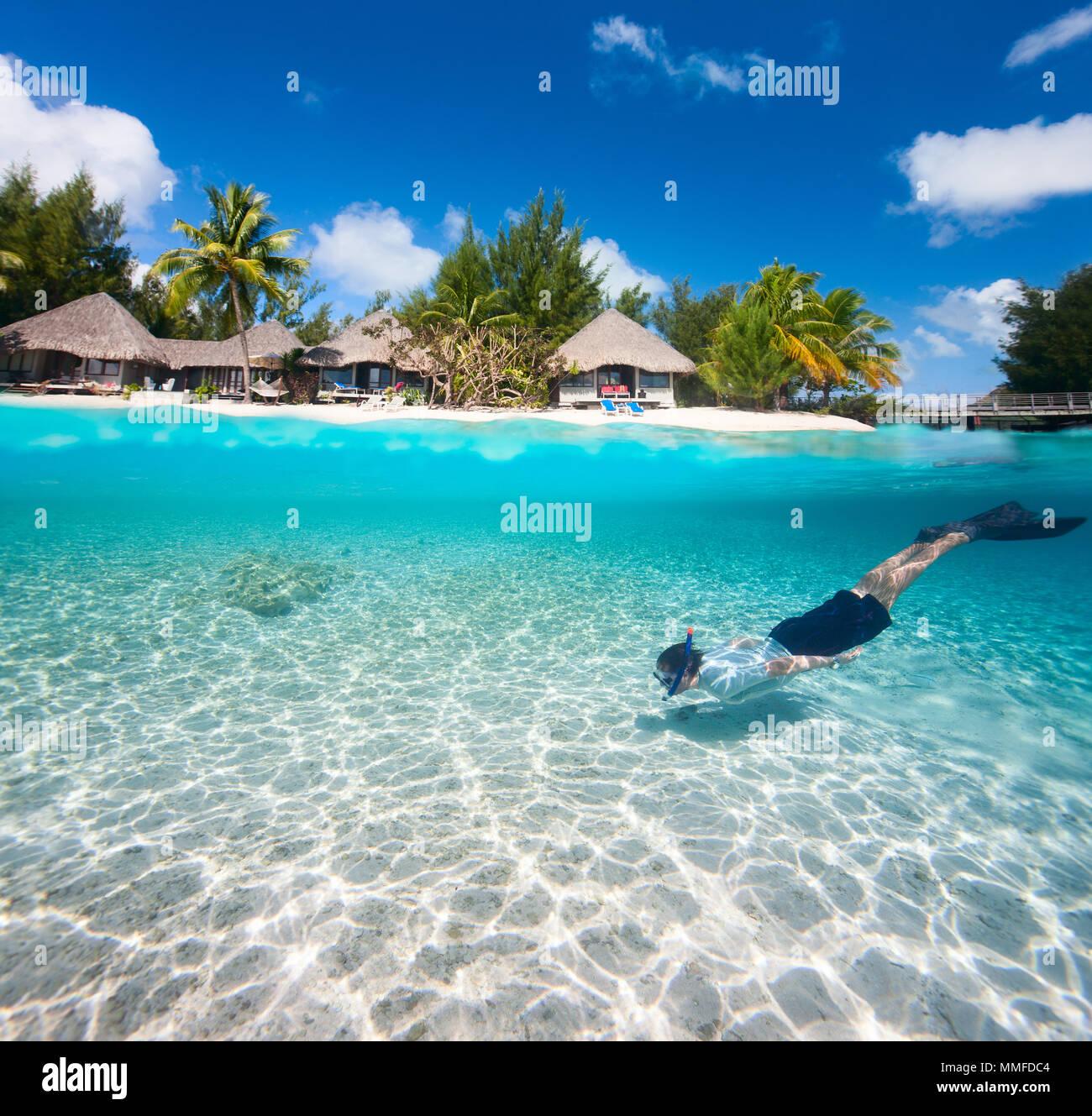 L'homme nage dans une lagune tropicale en face de l'île exotique Photo Stock