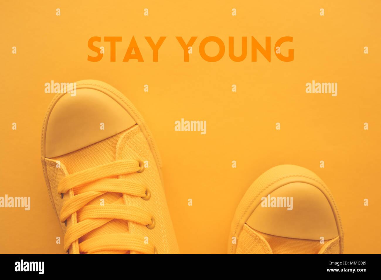 Rester jeune concept avec vue de dessus des pieds de l'adolescent dans l'élégant quartier de sneakers jaune Photo Stock