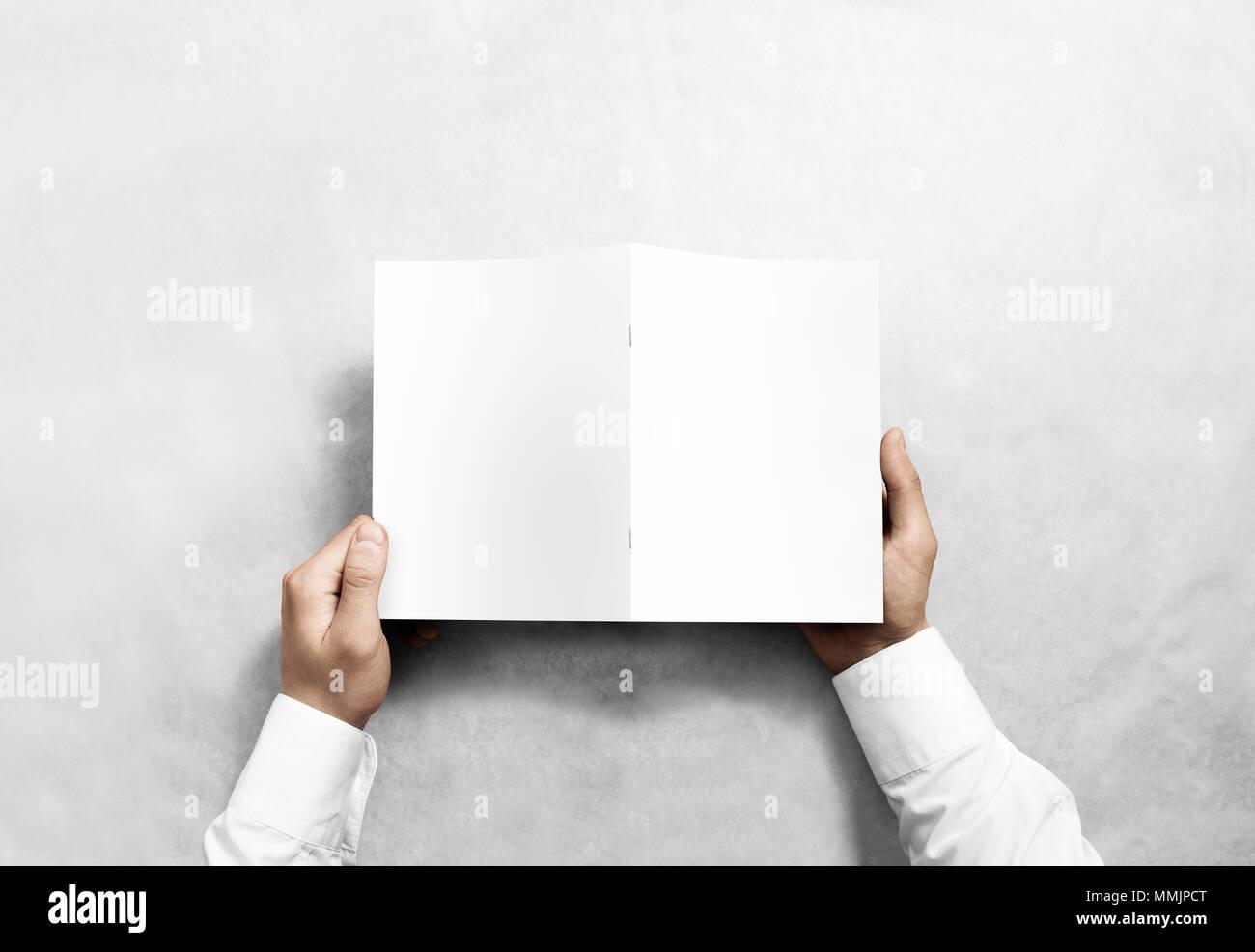 Hand holding blank white, maquette brochure retour Vue de côté. Notice de présentation du couvercle. Photo Stock