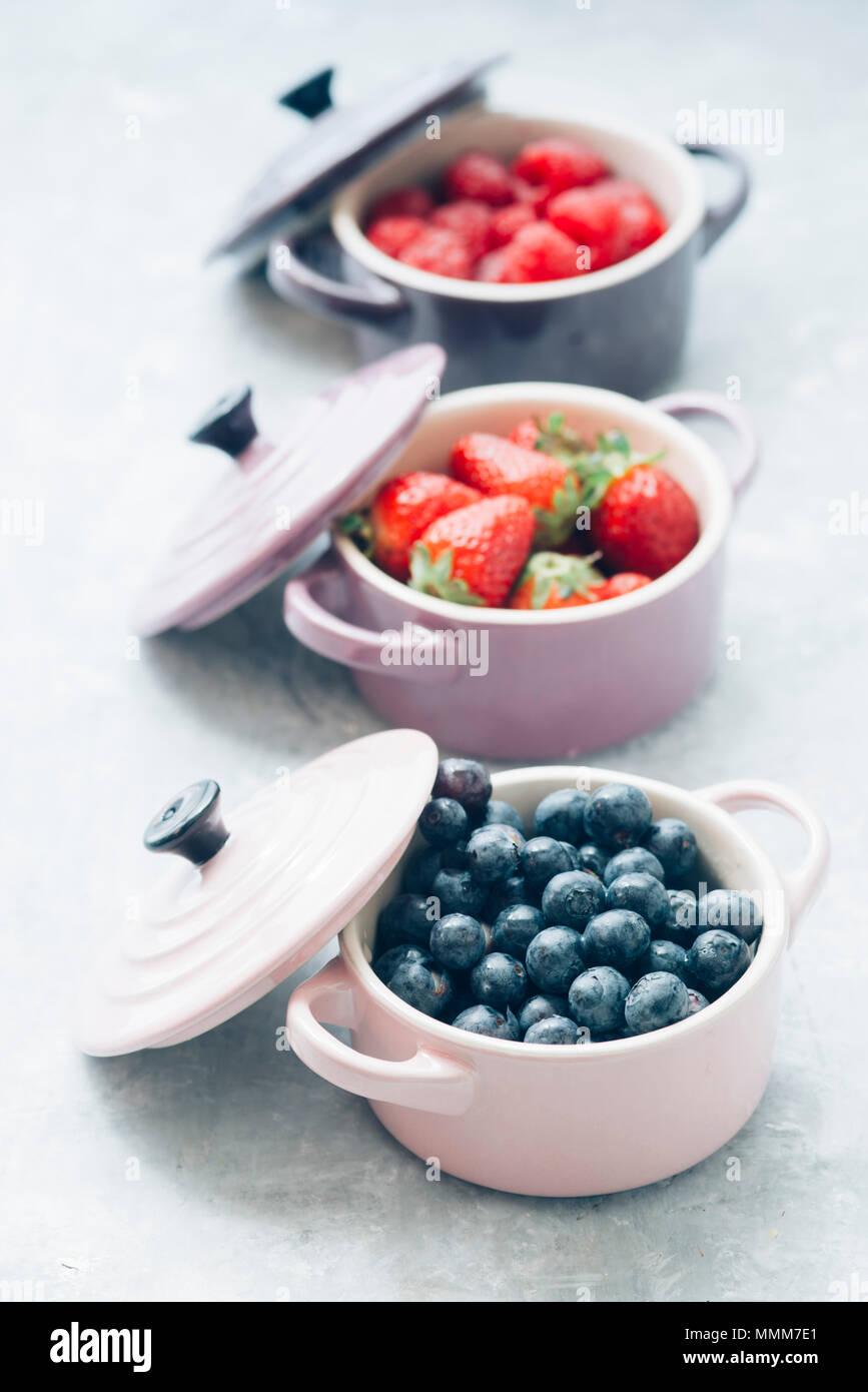 Les fruits d'été, l'arrière-plan Vue de dessus de l'intérieur de baies de couleur céramique cocotte, bleuets, fraises, framboises, télévision lay, tableau bleu. Detox et h Photo Stock
