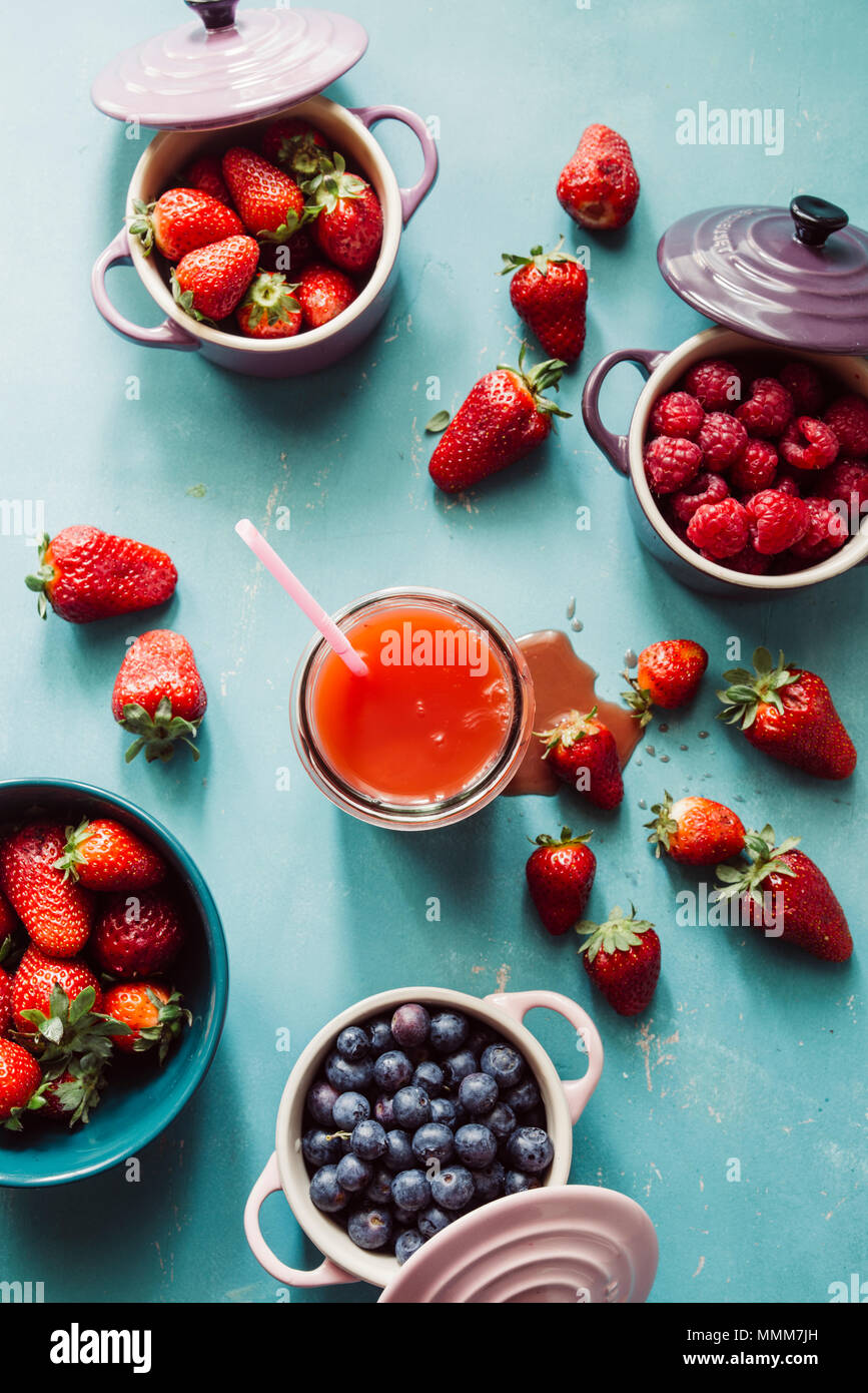 Les fruits d'été, l'arrière-plan Vue de dessus de l'intérieur de baies de couleur céramique cocotte, bleuets, fraises, framboises, poser à plat, bleu, table en verre avec un Photo Stock