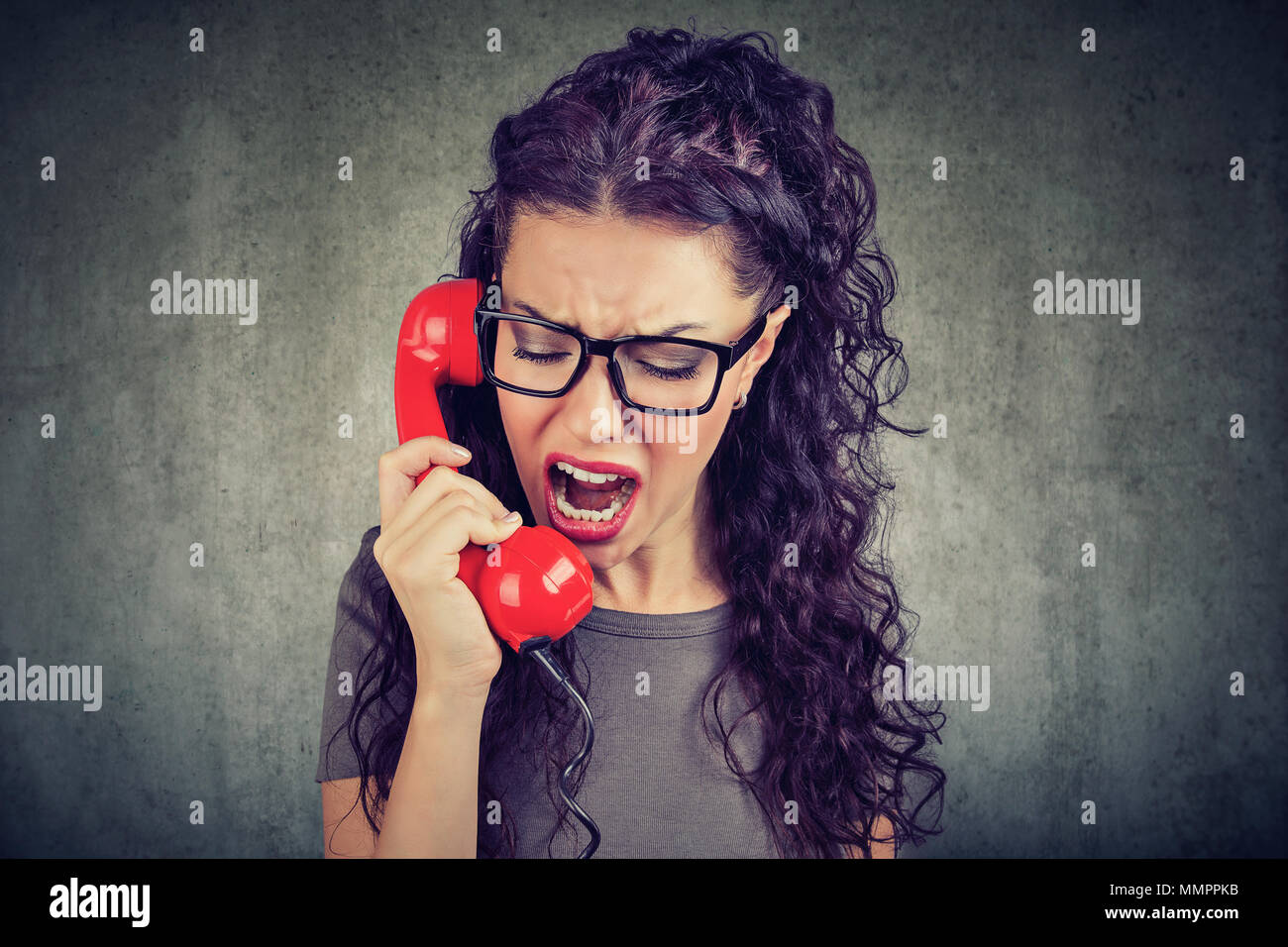 Jeune femme en colère crier au téléphone Photo Stock