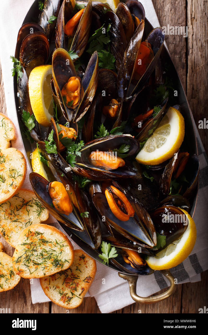 Moules à la française citron, le persil et l'ail close-up dans une marmite en cuivre et de grillé sur la table. Haut Vertical Vue de dessus Banque D'Images