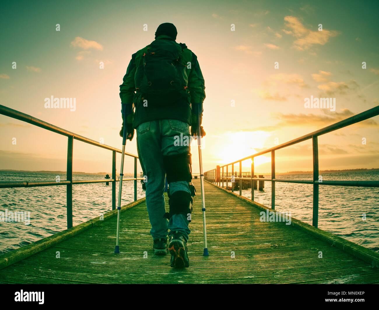 Homme blessé avec veste et l'avant-bras béquilles debout sur le pont dans la mer tôt le matin et de penser. Sombre silhouette nostalgique de sad lonely Photo Stock