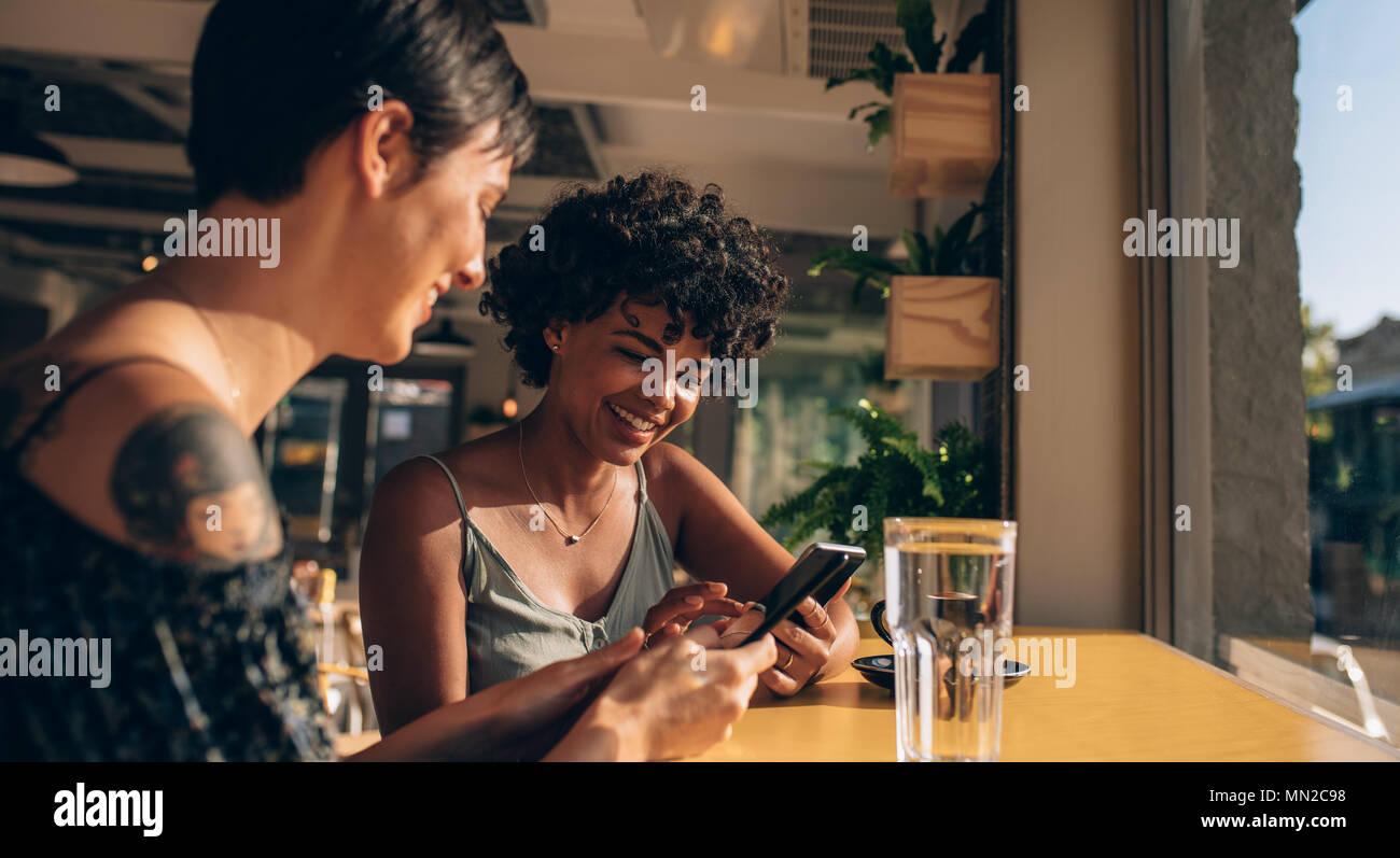 Two young women sitting at coffee shop en utilisant leur téléphone mobile. Les réseaux sociaux d'amis dans un café. Photo Stock