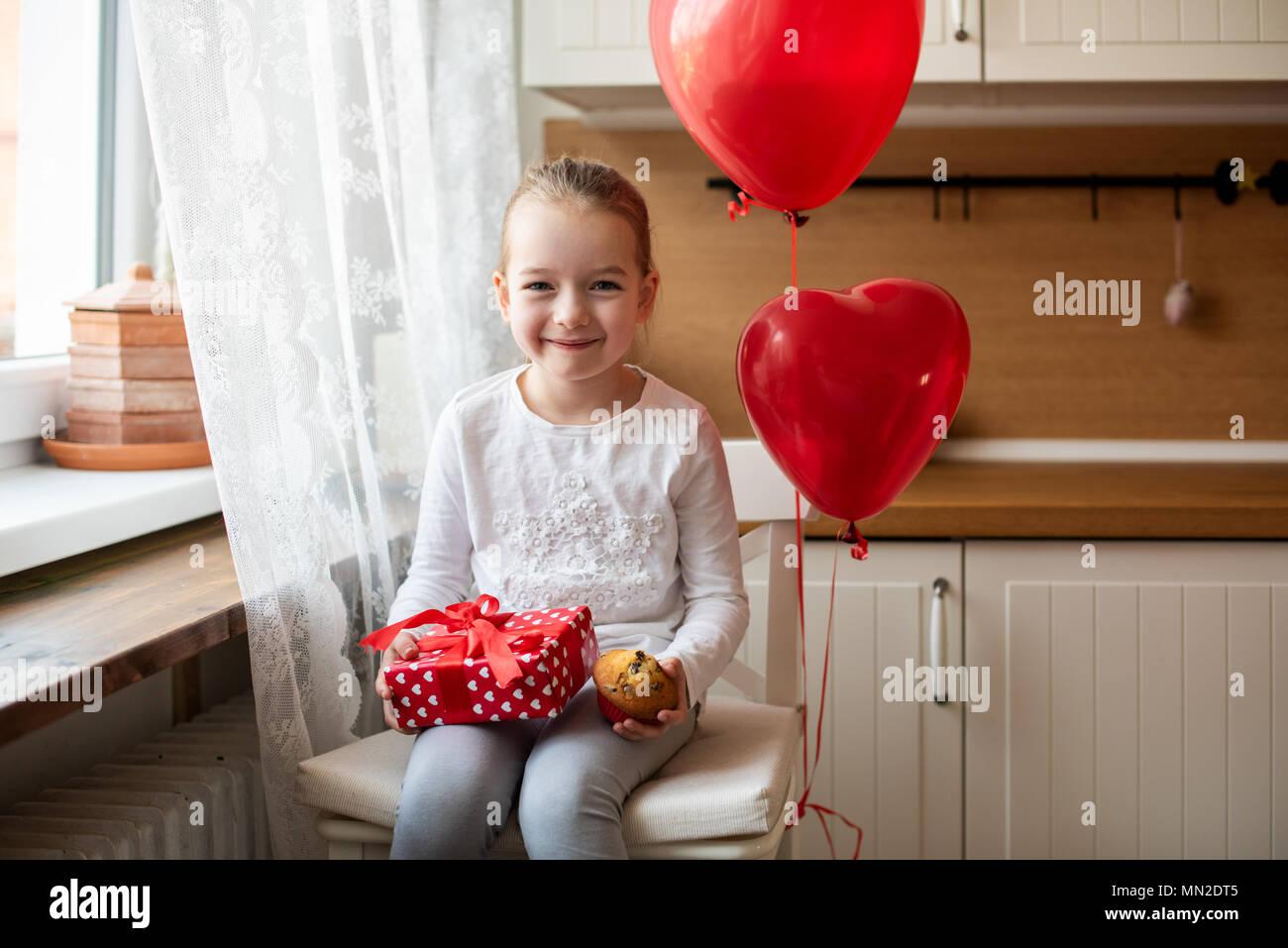 Cute girl bambin célébrer 6e anniversaire. Girl holding her birthday cupcake et joliment emballé présent, assis entouré par des ballons. Photo Stock