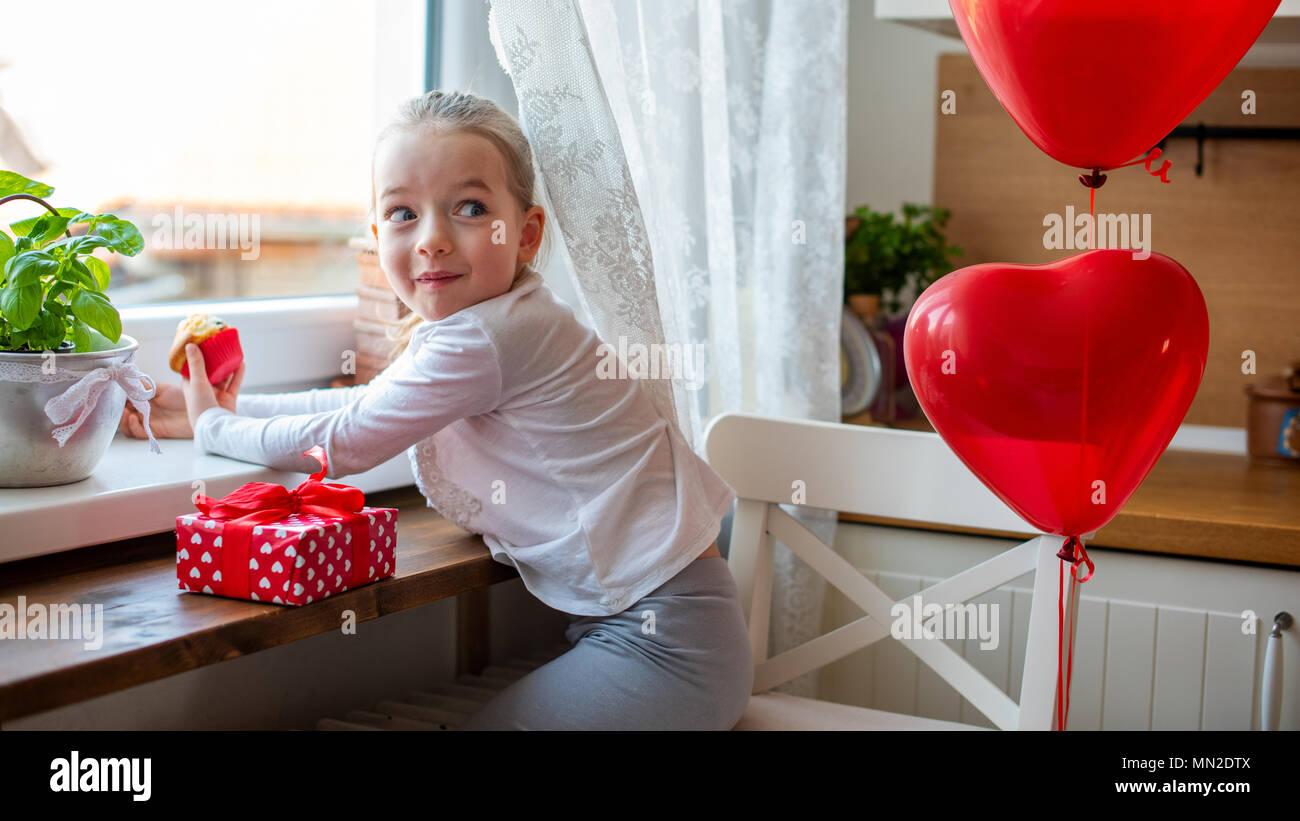 Cute girl bambin célébrer 6e anniversaire. Fille avec sourire espiègle manger son gâteau d'anniversaire dans la cuisine, entouré par des ballons. Photo Stock