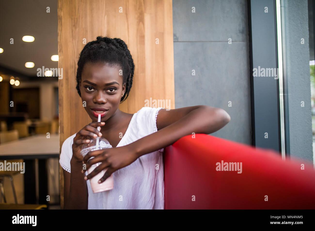 Photo de teint foncé positive des femmes afro-américaines ejoys bon repos à café, boissons alcoolisées. Les gens, les loisirs et l'alimentation concept Banque D'Images