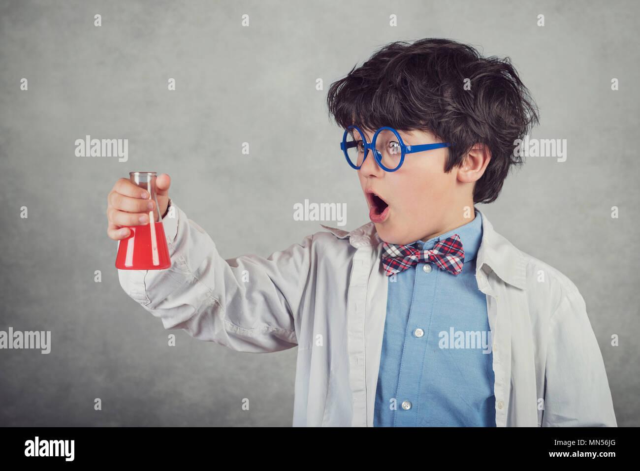 Garçon fait des expériences scientifiques sur fond gris Photo Stock