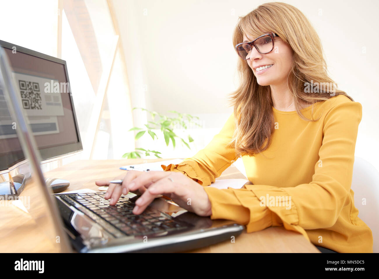 Smiling mature woman typing on laptop while sitting at desk et de travail au bureau. Photo Stock