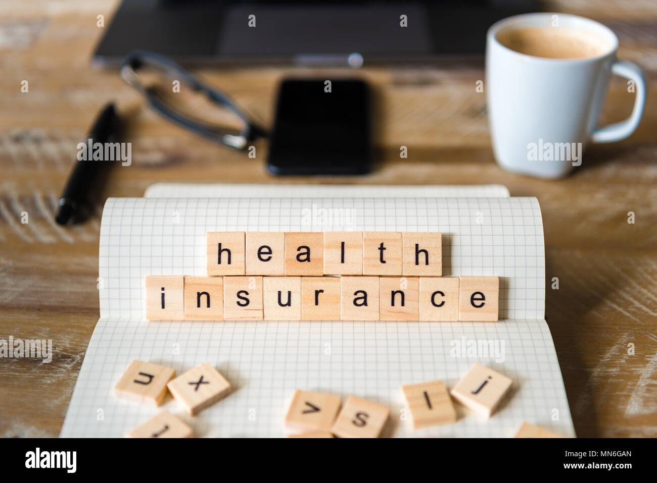 Gros plan sur ordinateur portable sur la table de bois, l'arrière-plan l'accent sur des pièces en bois avec des lettres formant des mots de l'assurance-santé. Photo Stock