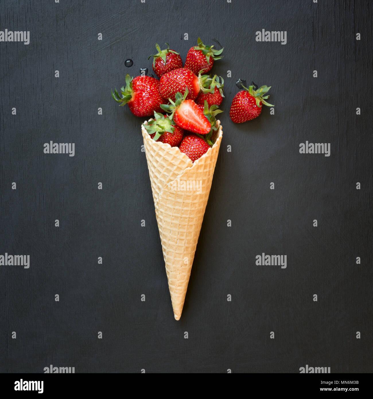 Produits frais bio fraise au ice cream cone sur noir. Photo Stock