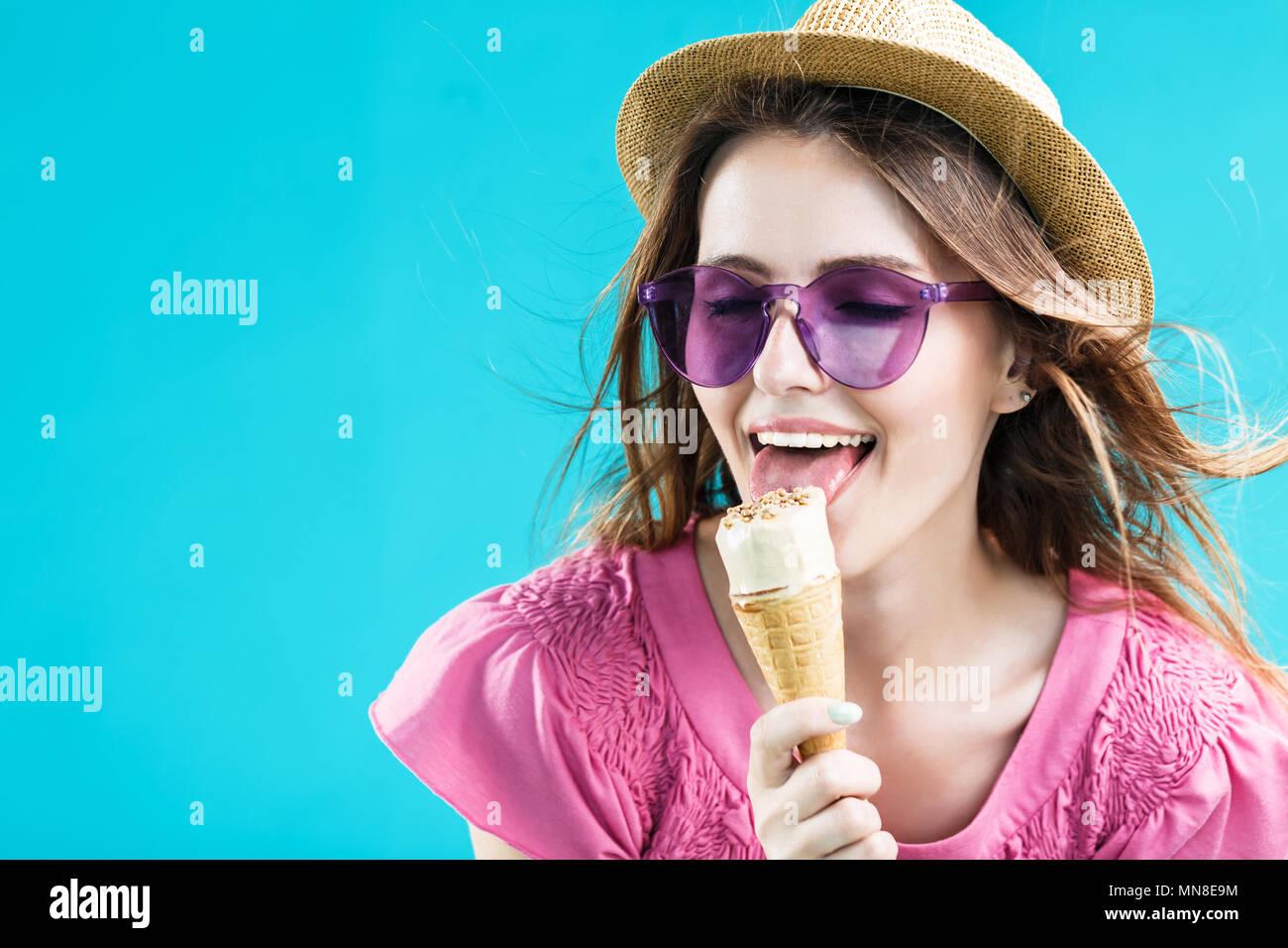 Très jolie jeune femme vêtue de rose shirt, chapeau et lunettes de soleil  lécher icecream b0745774273b