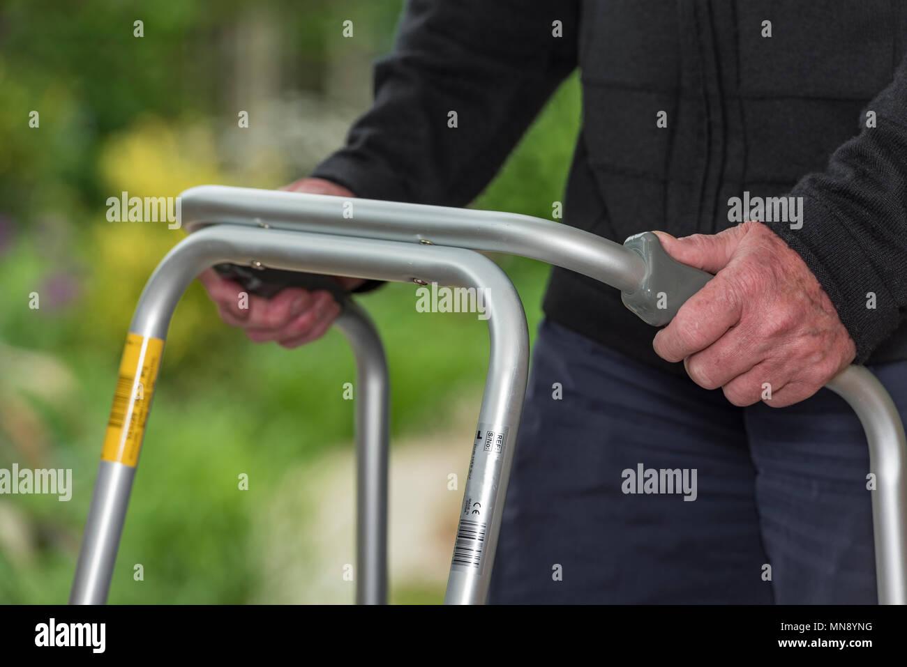 Personnes âgées, Senior caucasian man à l'aide d'un déambulateur ou zimmer aide à la mobilité. Photo Stock
