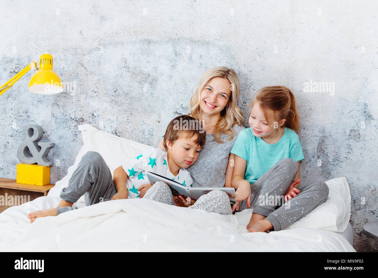 Belle mère est en train de lire une histoire à ses enfants Photo Stock