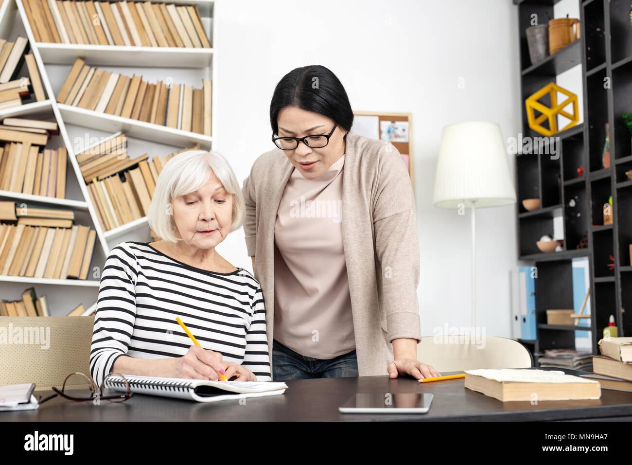 Tuteur attentif contrôle étude femme mature Photo Stock