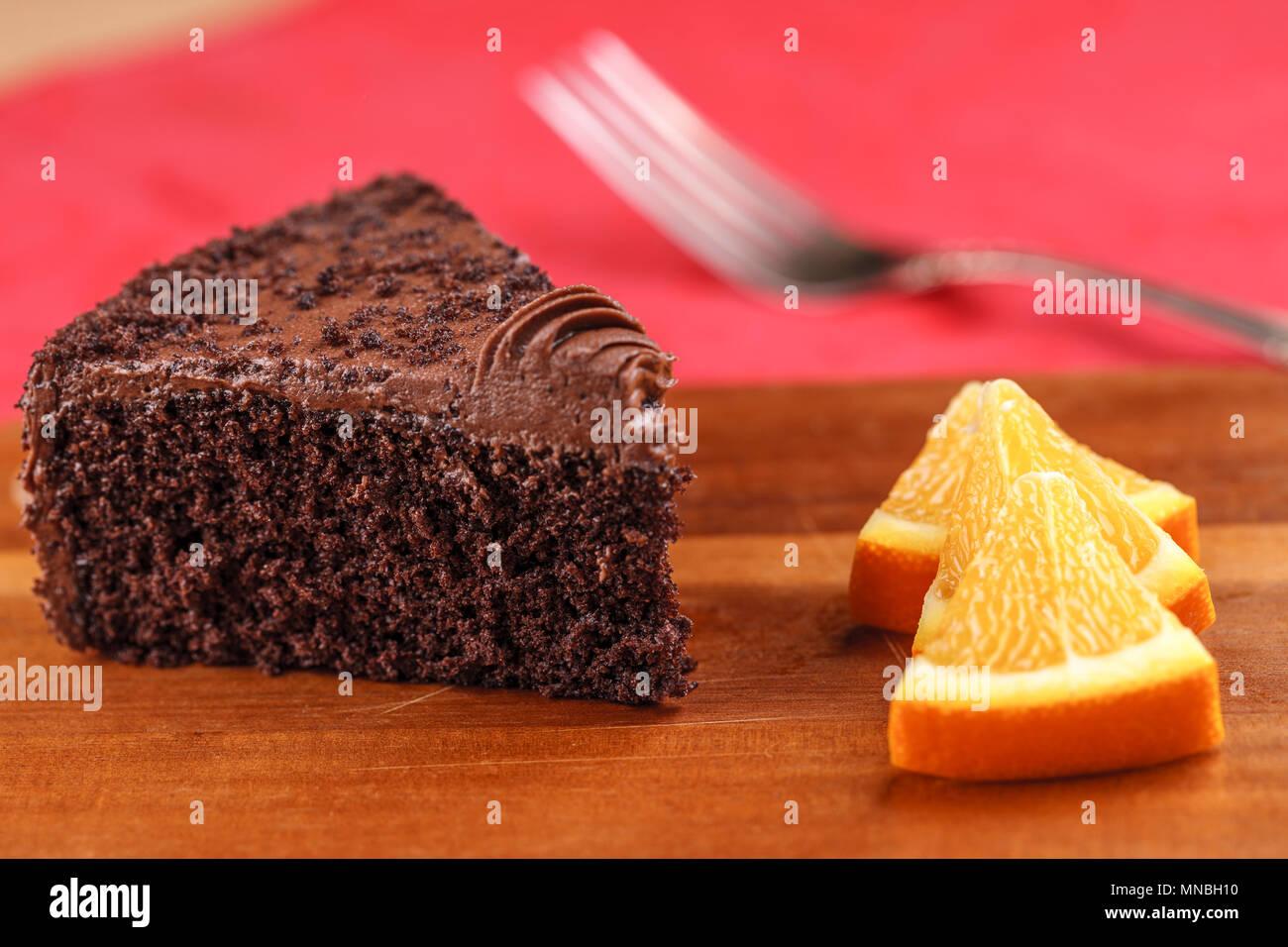 Un riche de gâteau au chocolat et des quartiers d'orange sur un conseil. Photo Stock
