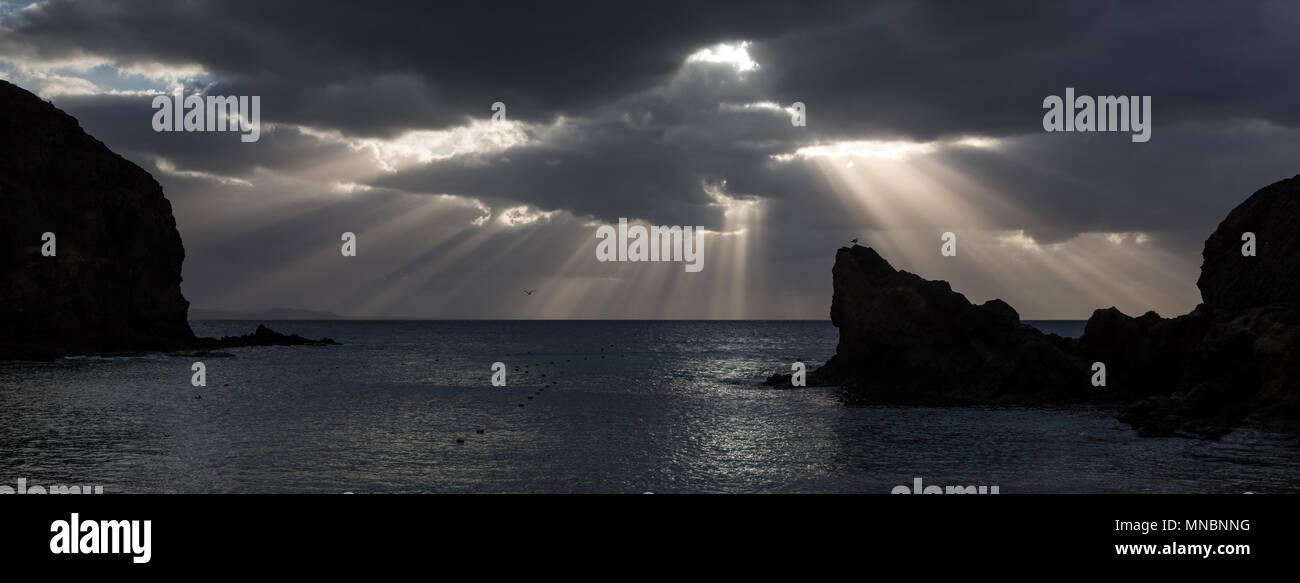 LANZAROTE, îles Canaries, Espagne: rayons de soleil à travers un nuage sur l'horizon à plage de Papagayo. Photo Stock