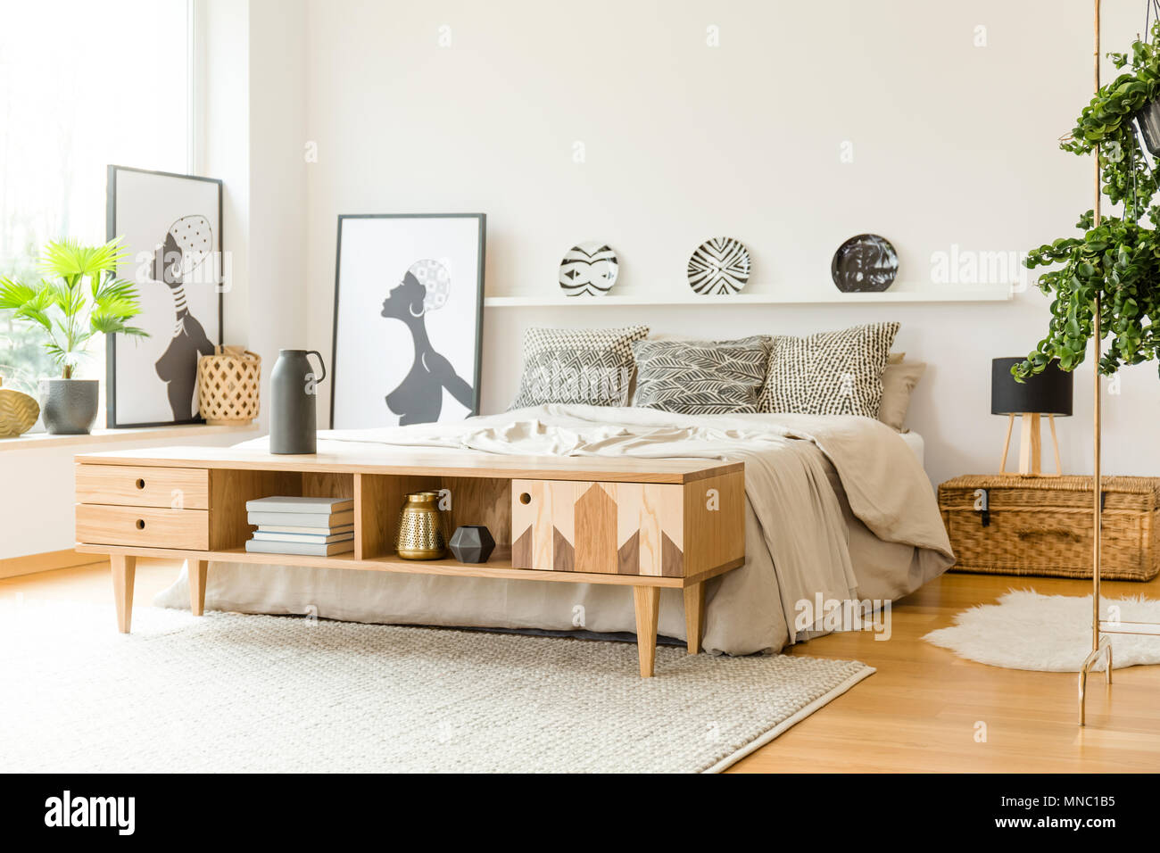 029b8d68ffb609 Armoire en bois près de lit dans la chambre à coucher boho intérieur avec  des affiches et des plantes
