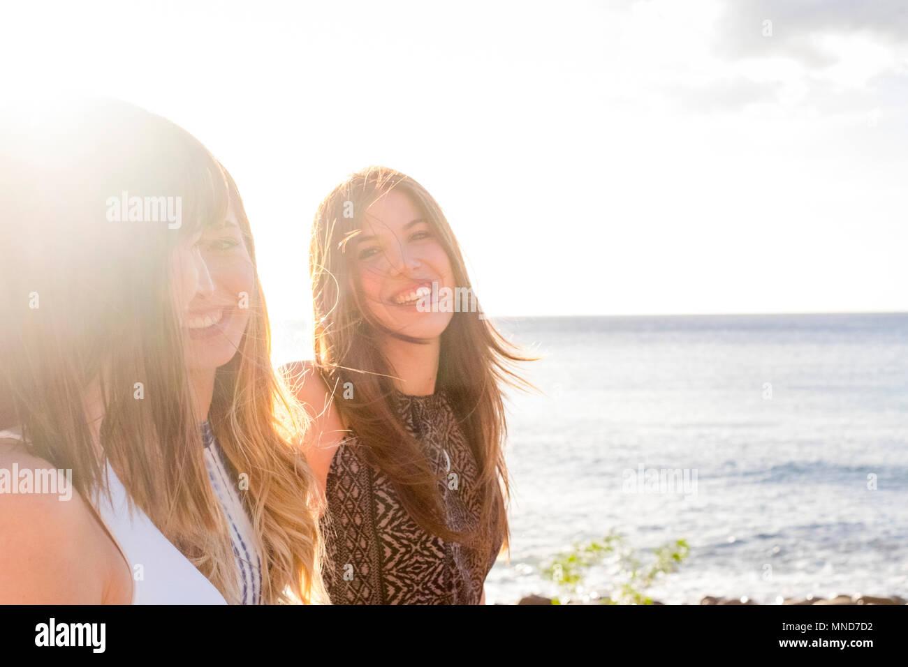 Trois jeunes femmes amis marcher ensemble sur un mur près de la plage à Ténérife. Profitez des locations sous un ciel bleu avec un soleil jaune. Mains en mains. Photo Stock