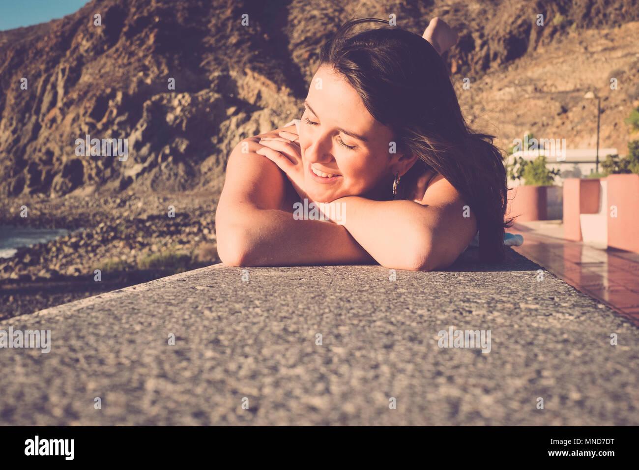 Les cheveux longs l'espagnol jeune femme erlaxing s'étendit sur un mur près de la plage. La lumière du soleil sur sa beauté visage, sourire et profiter du temps. Photo Stock