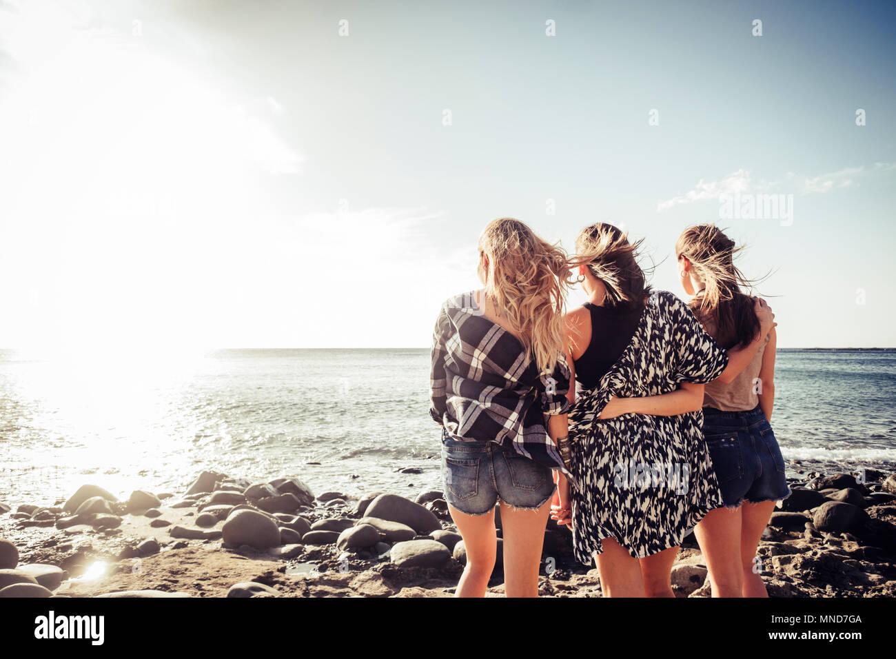 Groupe de trois jeunes filles de Nice à l'embrasser eux-mêmes à la ocean sunset en vacances. Moment de l'équipe plein d'émotions et de souvenirs. La lumière du soleil dans un b Photo Stock