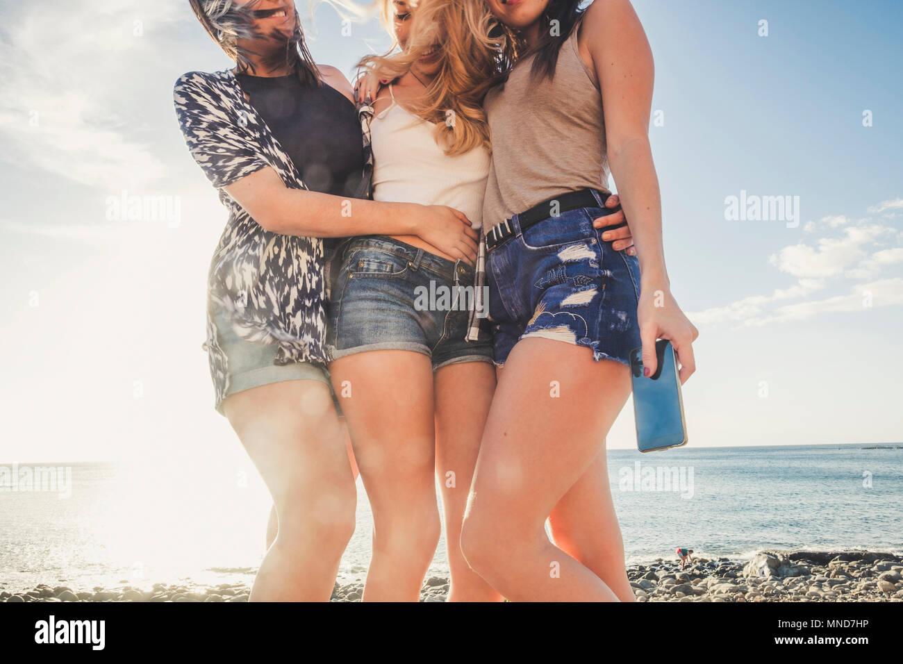 Groupe de femmes jeunes et beaux amis utilisent un smartphone.. La composition avec visages cutted et pas visibles. six jambes ensemble dans l'amitié. Photo Stock