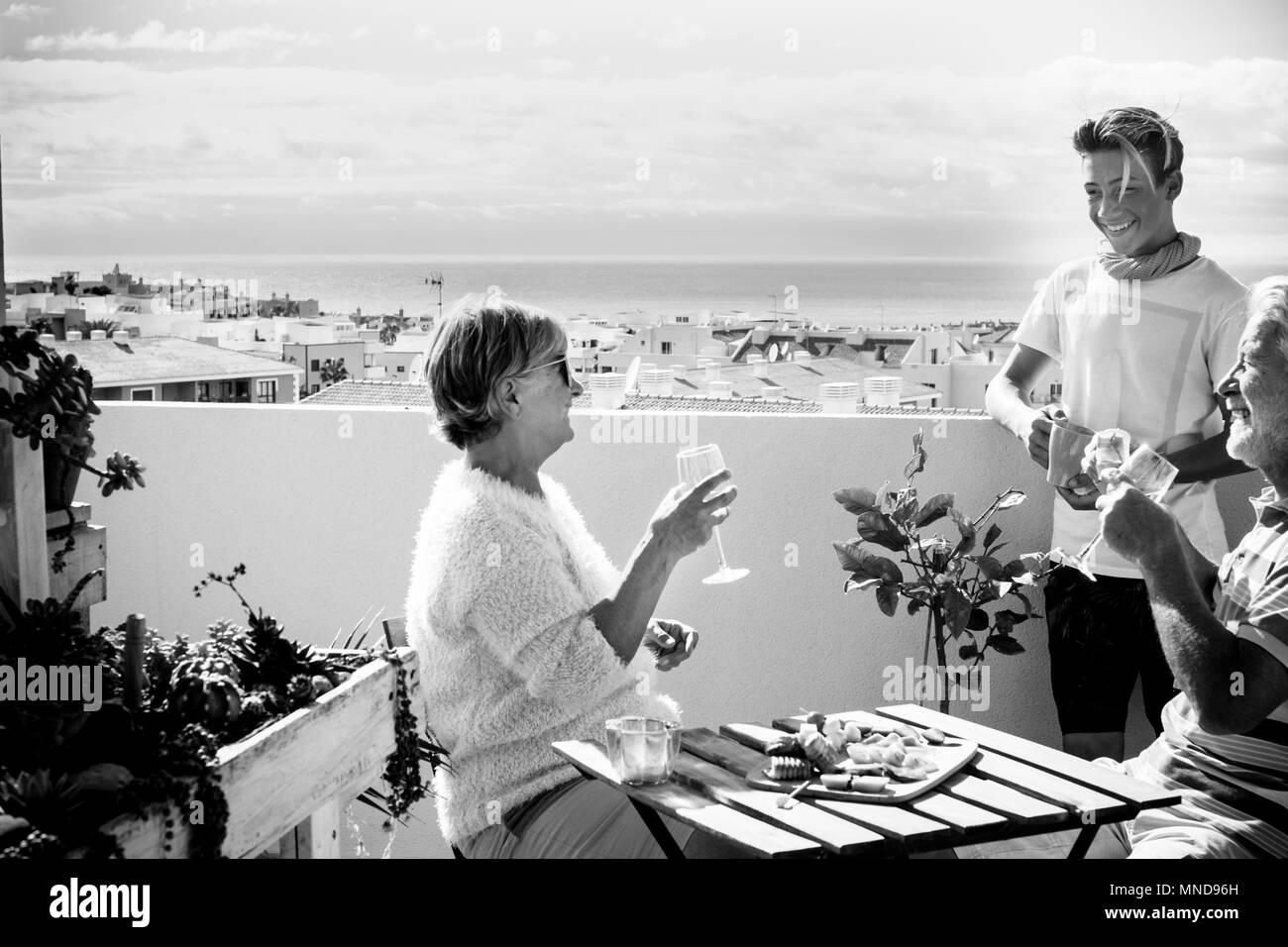 Grands-pères et neveu blonde jeunes restent sur la terrasse boire et manger de la nourriture sur la table. incroyable vue sur l'océan et un ciel clair pour le noir et blanc je Photo Stock