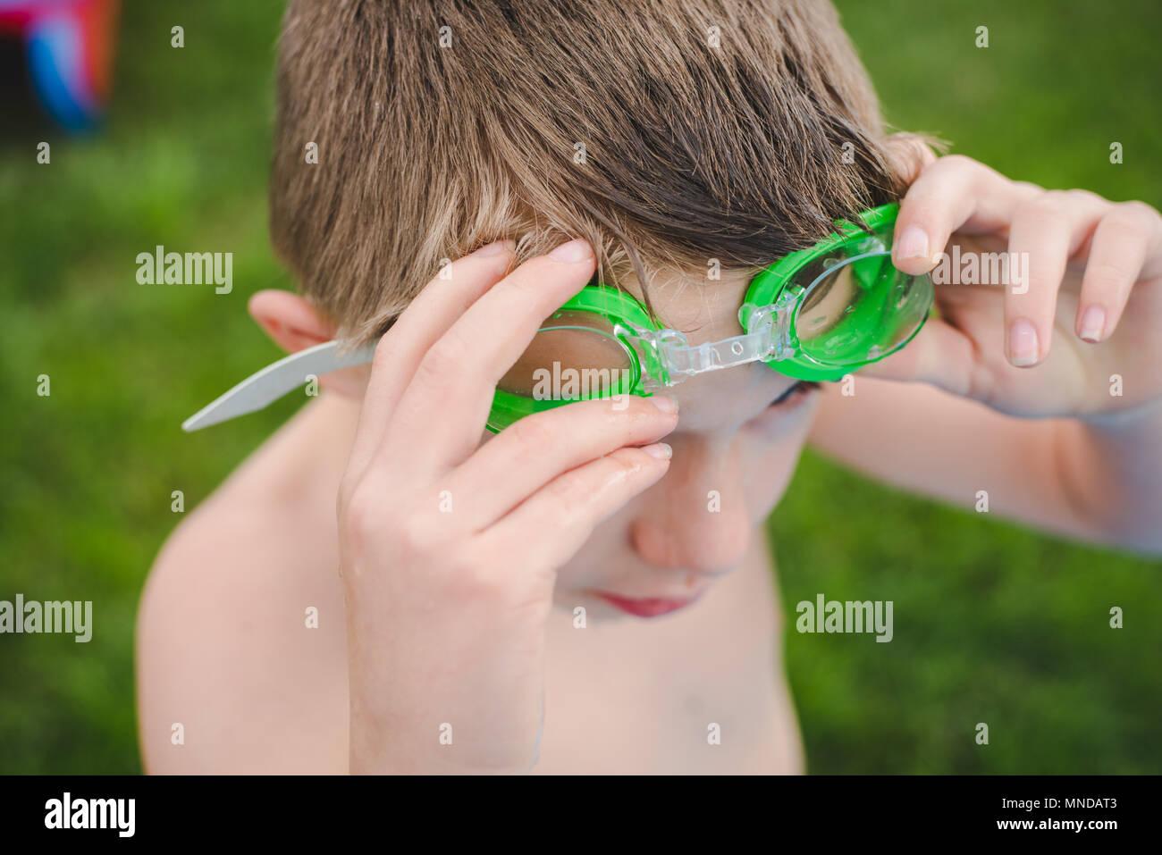 Un garçon portant des lunettes de natation vert sur une journée ensoleillée Photo Stock
