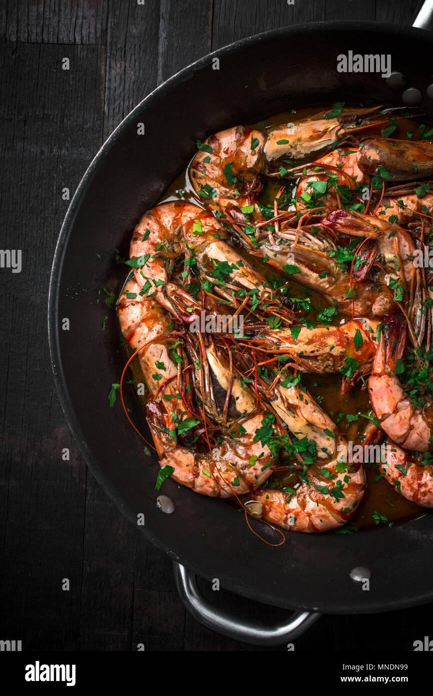 Poêlée de Crevettes Tiger dans une casserole. Recette classique - persil, ail, piment rouge et le vin blanc. Photo Stock