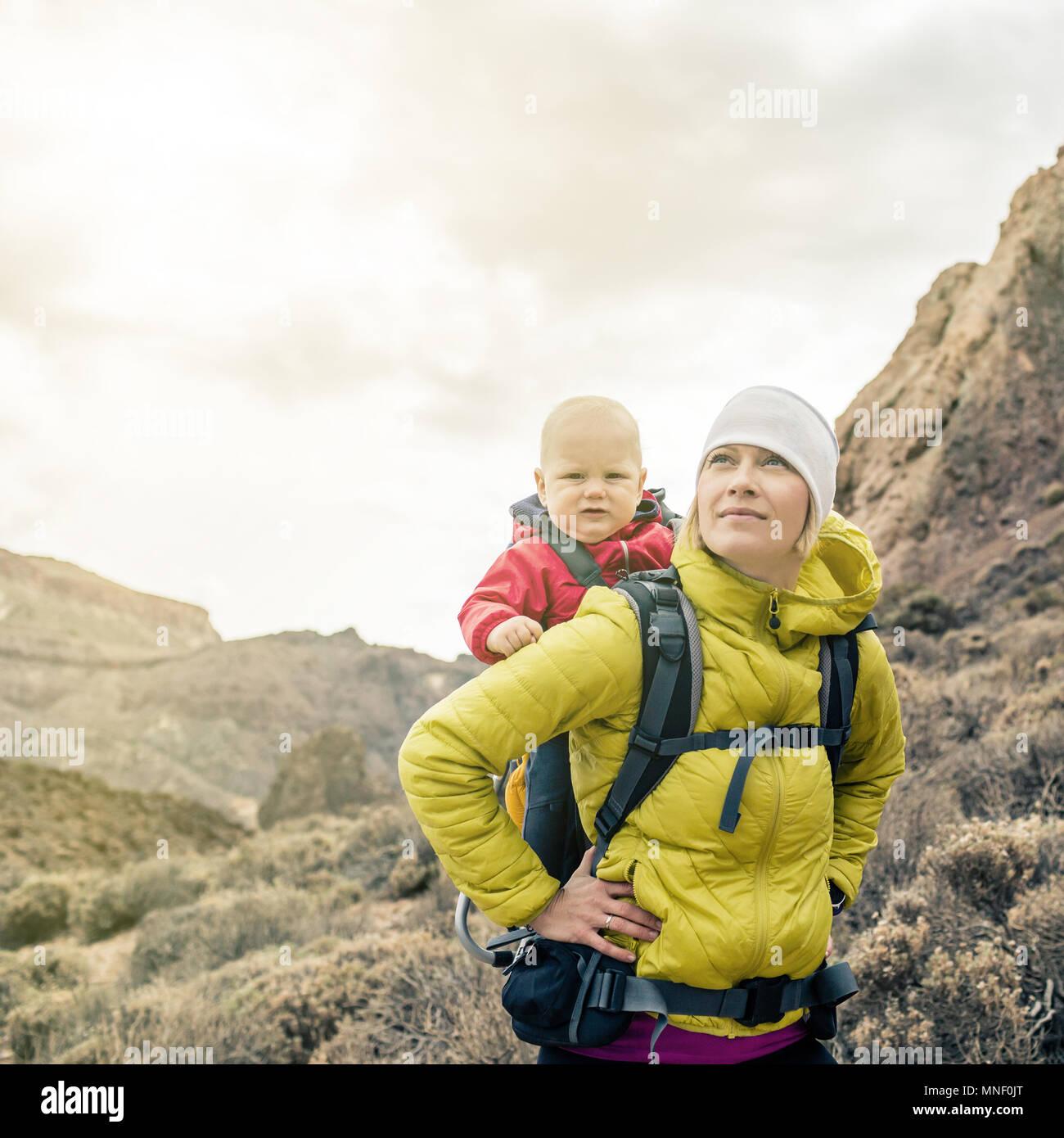 Mère de super-héros avec petit garçon voyager en sac à dos. Randonnées aventure avec enfant le voyage en famille dans les montagnes. Vacances voyage avec bébé carrie Photo Stock