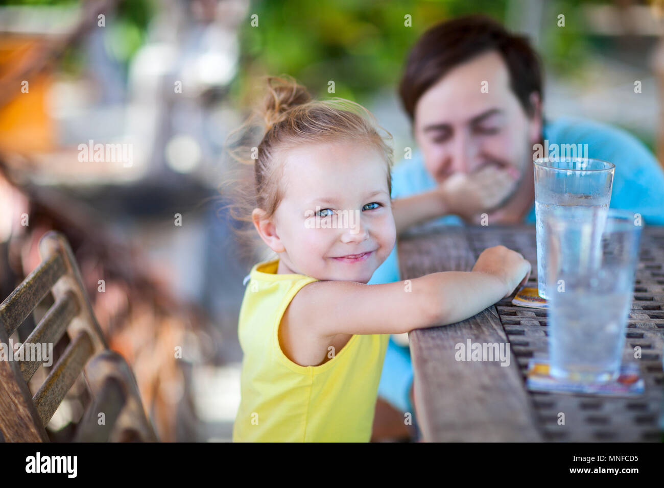 Happy little girl at outdoor restaurant ou un café avec son père Photo Stock