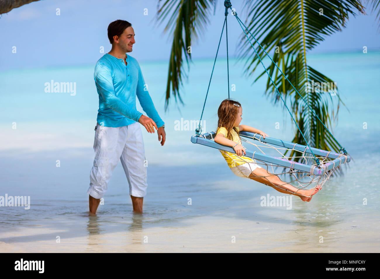 Heureux père et son adorable petite fille au Tropical Beach s'amusant sur une balançoire Photo Stock