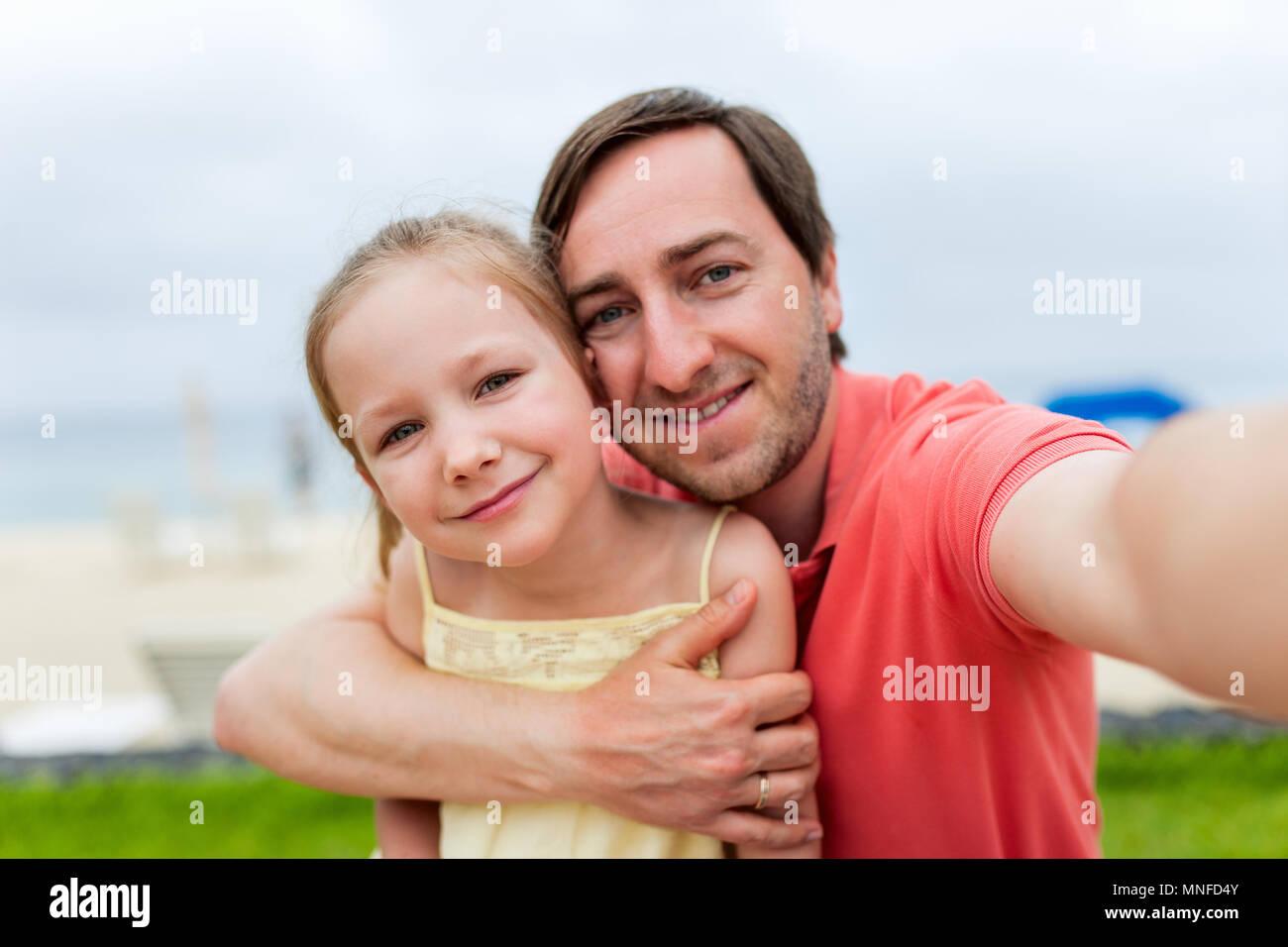 Père de famille heureuse et son adorable petite fille à plage tout en selfies Photo Stock