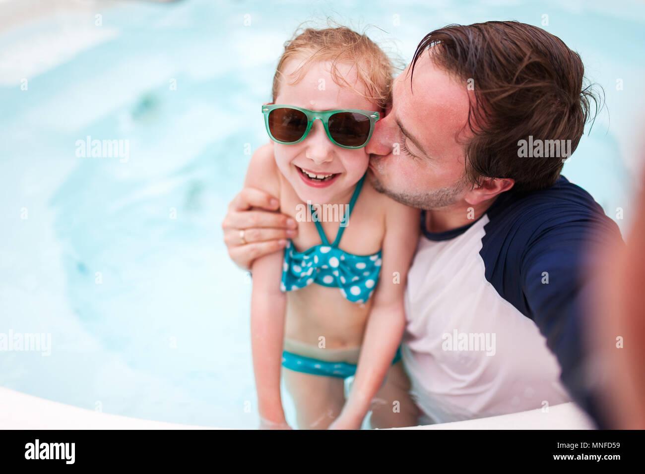 Père de famille heureuse et son adorable petite fille à l'extérieur piscine faire selfies Photo Stock
