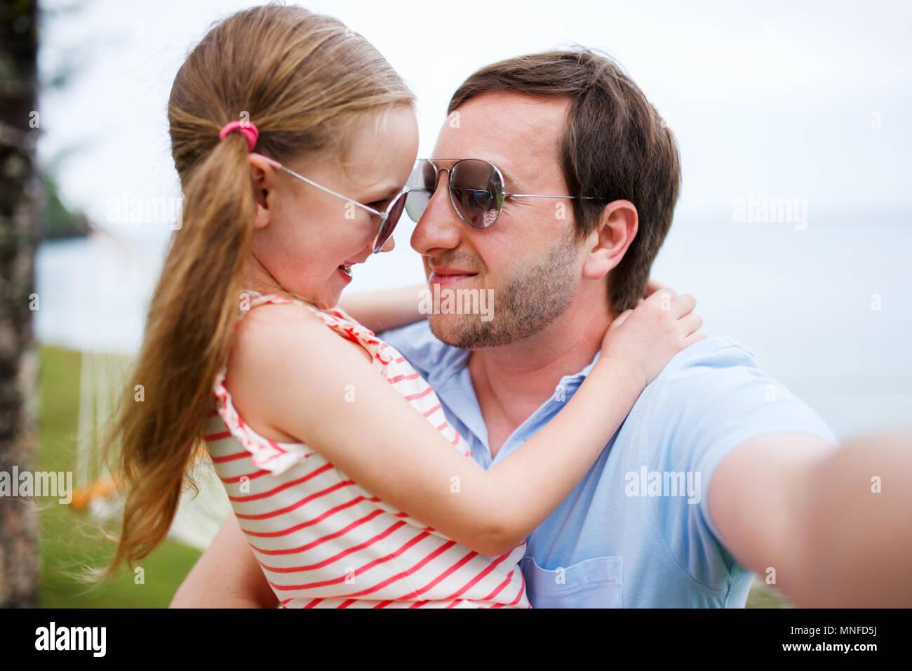 Père de famille heureuse et son adorable petite fille à la plage faire selfies Banque D'Images