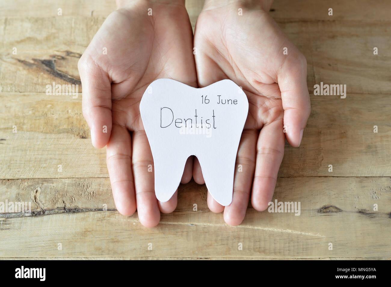 Rendez-vous chez le dentiste, coupures forme des dents écrire le mot que dentiste et date dans la main femme Photo Stock