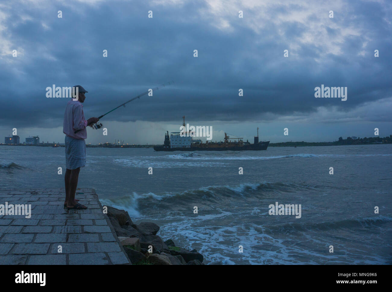 Un homme à la pêche en bord de fort Kochi Photo Stock