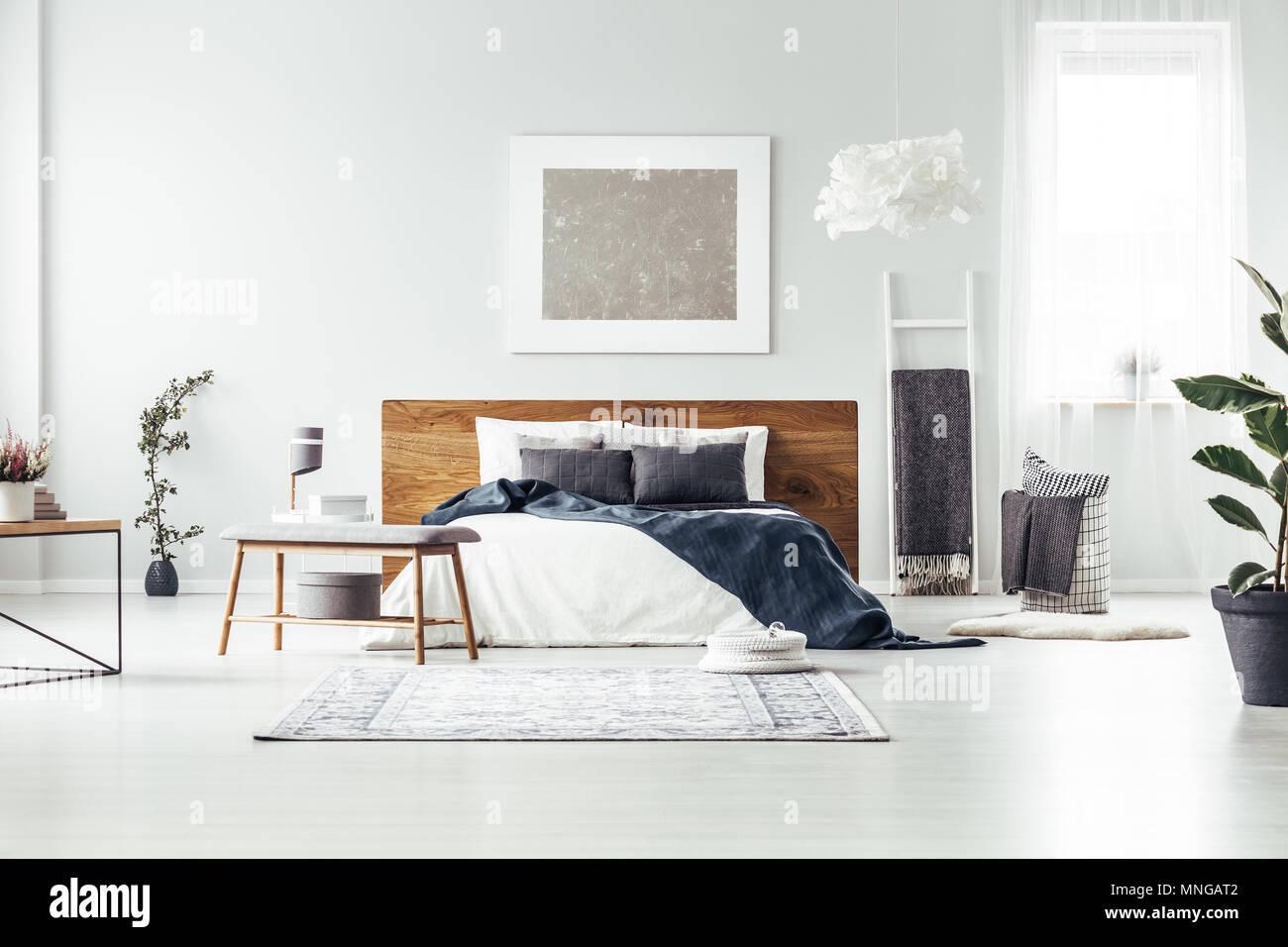 Banc en bois et de tapis près de king size avec couverture bleu ...
