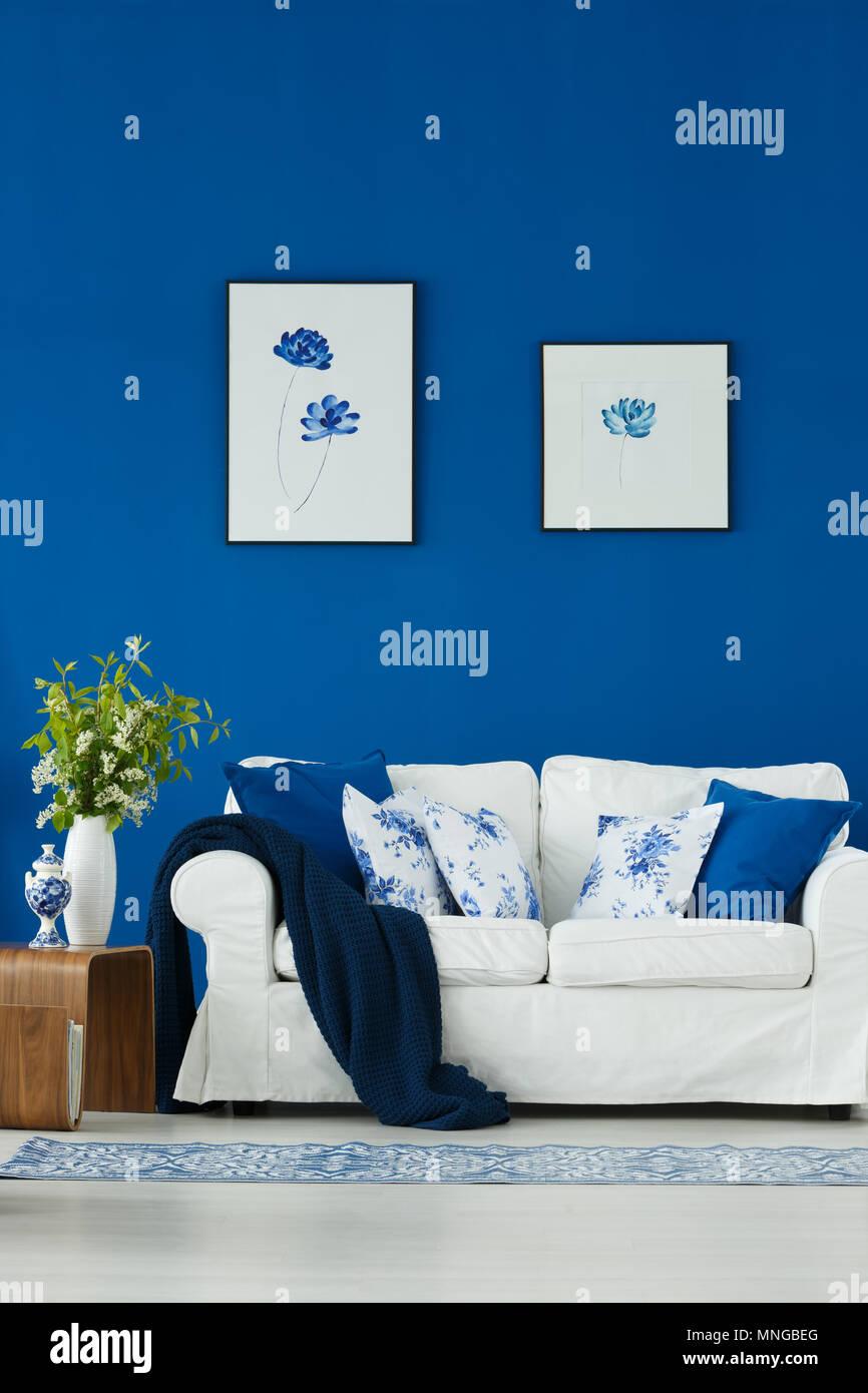 Canapé blanc contre mur bleu avec des affiches Banque D'Images